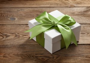 Beautiful gift box with a bow on the table from the old boards
